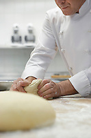 Chef preparing dough in kitchen