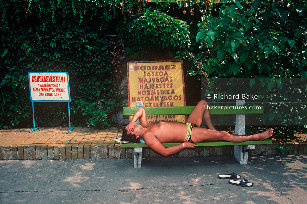 A 1990s Hungarian gentleman snoozes in the shade of trees at the Szechenyi spa hotel, on 13th June 1990, in Budapest, Hungary.