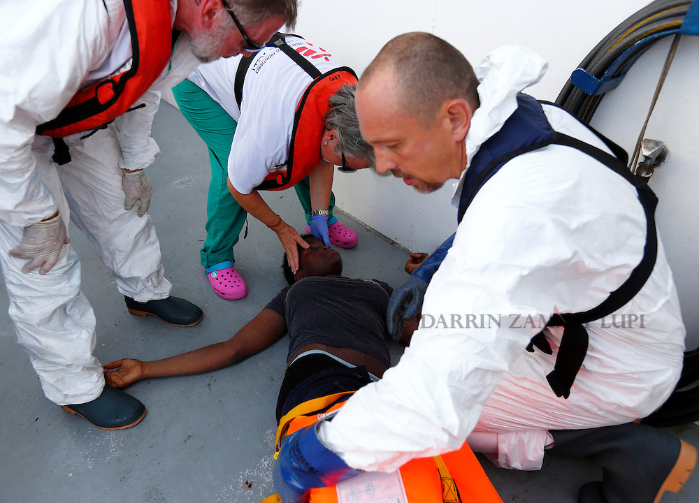 Medecins san Frontiere (MSF) medics examine a semi-conscious migrant who was brought onto the Migrant Offshore Aid Station (MOAS) ship MV Phoenix some 20 miles (32 kilometres) off the coast of Libya, August 3, 2015.  118 migrants were rescued from a rubber dinghy off Libya on Monday morning . The Phoenix, manned by personnel from international non-governmental organisations MSF and MOAS, is the first privately funded vessel to operate in the Mediterranean.<br /> REUTERS/Darrin Zammit Lupi <br /> MALTA OUT. NO COMMERCIAL OR EDITORIAL SALES IN MALTA