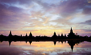 The sunset reflects in a puddle of rainwater over the temples of Bagan, Burma, 2003.