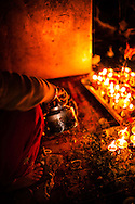 Women prepare the liquid concoction for butter lamps at a shrine in the Thamel District in Kathmandu, Nepal.
