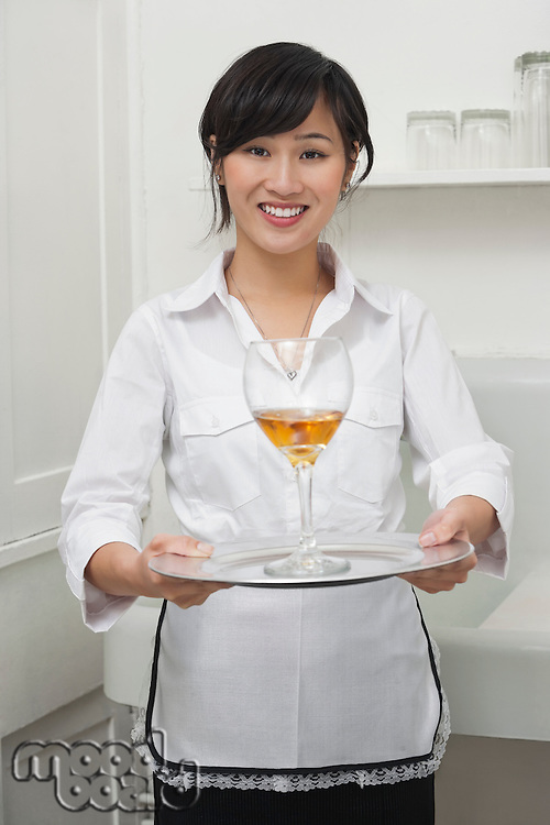 Portrait of female housekeeper serving wine in goblet