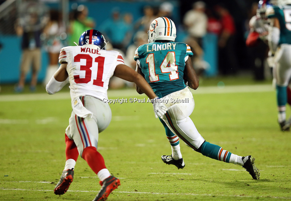 Miami Dolphins wide receiver Jarvis Landry (14) is chased by New York Giants defensive back Trevin Wade (31) after catching a second quarter pass during the NFL week 14 regular season football game against the New York Giants on Monday, Dec. 14, 2015 in Miami Gardens, Fla. The Giants won the game 31-24. (©Paul Anthony Spinelli)