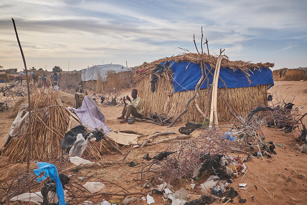 A man leans against a shelter at a camp of displaced people in the neighbourhood of Chateau, Diffa, Niger on February 13, 2016. The camp is mixed between displaced people from Niger, Nigeria and Chad. They have fled attacks by the militant group Boko Haram on their villages and it's ongoing conflicts with the armies of each country. Caritas undertook a distribution of mosquito nets, cooking pots, sleeping covers, hygiene kits, clothes and cash transfers to the displaced. 228 households received support from Caritas among an estimated 1500 households in the  vicinity of Chateau. There is still great need. There is no school system in place for the children and the housing is not adequate for many as more people arrive each day escaping hostilities.