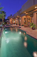 Pool with house exterior at dusk