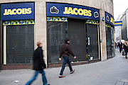 Pedestrians walk past a Jacobs camera shop that has recently closed down near Bank, London, United Kingdom.  Jacobs Photo Digital, a family-run British business, went into administration in June 2012.  The retail business was established in 1939, but has been a victim of the economic slowdown as there has been a shift in purchasing toward internet-based retailers.