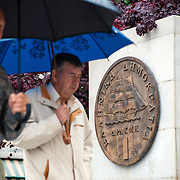 Greeks walking under rain by a plaque portraying an old drachma coin, which was replaced by the euro in 2002, outside Athens City Hall