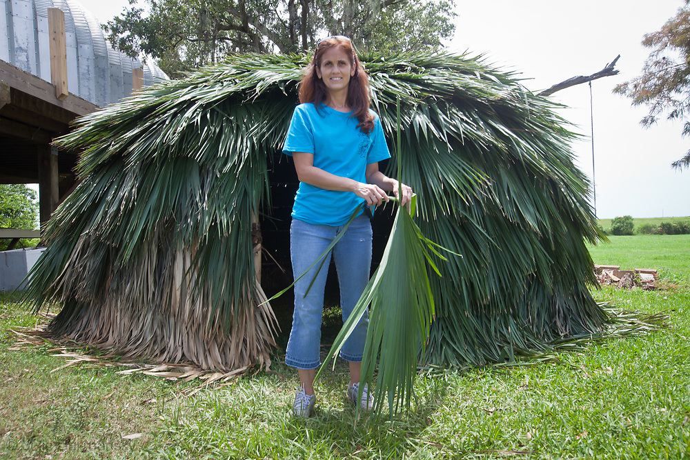 Michelle Matherne , a Pointe-au-Chien Indian in front of a Palmetto hut the Pointe-au-Chien tribes elders built during a summer camp session for the tribes' children to expose them to their disappearing culture.