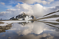 Whatcom Peak shrouded in clouds and reflected in upper Tapto Lake, North Cascades National Park Washington
