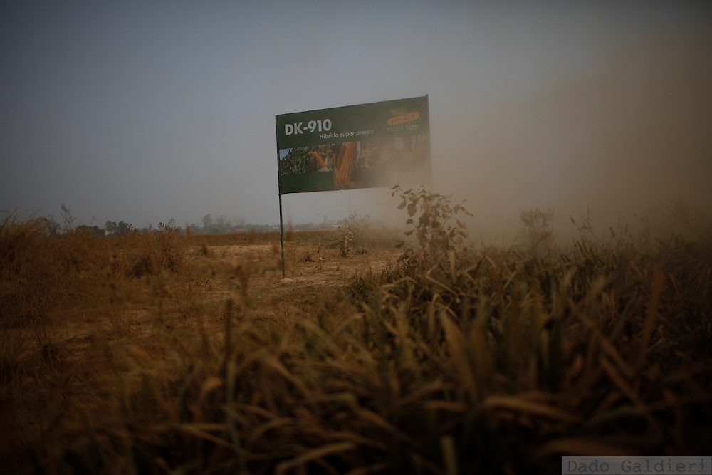 A banner advertises genetically modificated corn seeds aside a road leading to Pailas river and agribusiness farm plots near the village of San Pedro, Santa Cruz, Bolivia, Wednesday, Aug. 25, 2010.(Hilaea Media/Dado Galdieri).