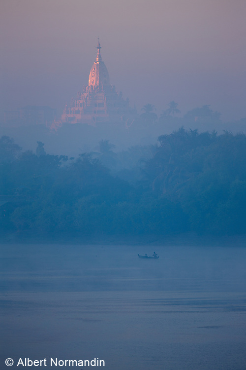 Early light on Malla Mu temple and boat on Ayeyarwady River in mist
