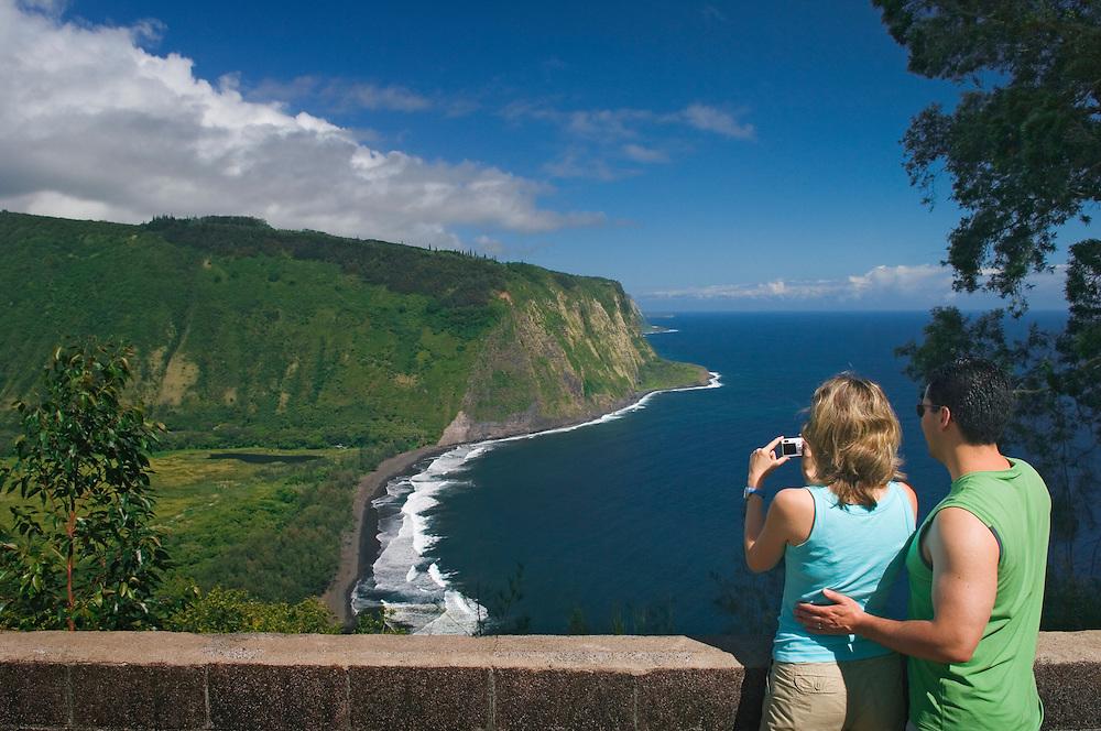 Couple taking photo with digital camera at Waipio Valley Lookout, Hamakua Coast, Island of Hawaii..#0604919