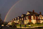 With a brief rainbow arcing overhead, a pedestrian carrying an umbrella walks along a south London residential street, passing sunlit Edwardian period homes after heavy rainfall, on 25th February 2020, in London, England.