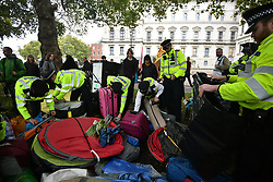 © Licensed to London News Pictures. 07/10/2019. London, UK. Police search equipment belonging to Extinction Rebellion protestors at the back entrance to Downing Street in Westminster . Activists will converge on Westminster blockading roads in the area for at least two weeks calling on government departments to 'Tell the Truth' about what they are doing to tackle the Emergency. Photo credit: Ben Cawthra/LNP
