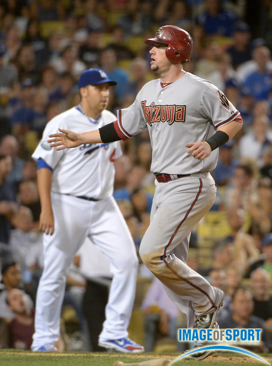 Aug 31, 2012; Los Angeles, CA, USA: Arizona Diamondbacks third baseman Chris Johnson (28) crosses the plate to score in the fifth inning as Los Angeles Dodgers pitcher Aaron Harang (44) watches at Dodger Stadium. The Diamondbacks defeated the Dodgers 4-3 in 11 innings.
