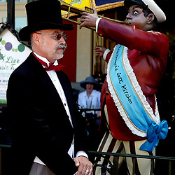 A man dressed in tails walks past a statue of a man playing a jazz horn on Dapper Day in Downtown Disney in Anaheim, Calif., Sunday, April 23, 2017.