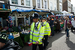 © London News Pictures. 30/08/2014. London, UK. Police officers on Portobello Road in West London today (30/08/2014). A murder investigation has been launched after a Man aged in his fifties died of stab wounds in the early hours of this morning on Portobello Road. Respect party politician George Galloway was alleged assaulted in the same area late yesterday evening. Photo credit : Ben Cawthra/LNP