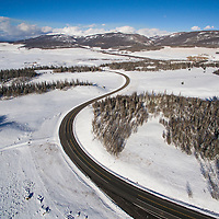 USA, Colorado, Creede, Aerial view of winding highway and snow-covered forest in the Rio Grande Valley