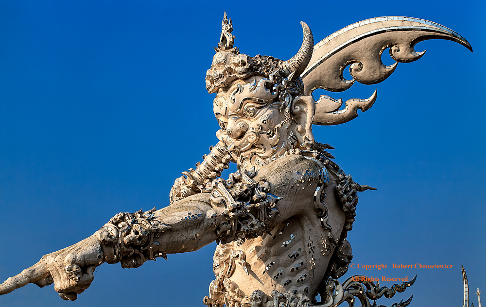 Guardian: An intricately detailed statue of a guardian of heaven, is quite ferocious as he is decorated with a crown, bracelets, arm bands, rings and other adornments made of skulls and bones, while holding a sword on high that has a shaft made of the bones of a spine, at Wat Rong Khun (the White Temple), Chiang Rai Thailand. <br /> <br /> <br /> The work was designed by Thai artist Chalermchai Kositpipat.
