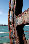rusty wheel sculpture with distant view of the North Shore at Wynyard Quarter, Auckland Viaduct, New Zealand