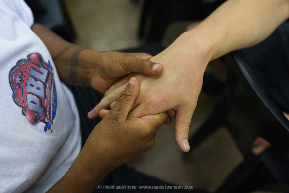 Julie Tshabalala, South African women's welterweight and middleweight champion, massaging the hands of Joe Eades, whom she coaches, ahead of an amateur boxing tournament in Cosmo City, a large low-income housing development 40 minutes north of Johannesburg, South Africa. It will be Eades' first fight.