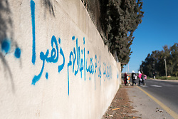 18 March 2019, Bethlehem, Occupied Palestinian Territories: A group of children head to Al Minya school. On the wall in Arabic, is a poem about how to have good manners. Ecumenical Accompaniers from the World Council of Churches' Ecumenical Accompaniment Programme in Palestine and Israel spend the morning doing a 'school run', by which they offer a peaceful protective presence for Palestinian children as they go to school at Al Minya.  With Israeli settler communities nearby, strong military presence, and a high-speed road passing just by the school entrance, an international presence can help ensure safe passage for the children.