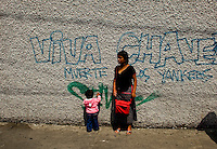 A woman and small child stand in front of graffiti as citizens take to the streets as a day of protest in connection with Guatemala's President Alvaro Colom fill the Central Plaza in Guatemala City May 17, 2009. . Thousands of protesters took to the streets of the capital  Sunday in two separated rival marches, one in support of the President and one denouncing President Alvaro Colom who was accused this week of murder, money laundering and having ties with narco-traffickers.(Darren Hauck)