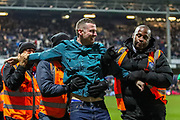An excited Sheffield Wednesday fan gets escorted off the pitch by stewards during the The FA Cup match between Queens Park Rangers and Sheffield Wednesday at the Kiyan Prince Foundation Stadium, London, England on 24 January 2020.