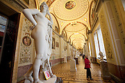 A tourist views murals and statues at the vast State Hermitage Museum in St. Petersburg, Russia. (From the book What I Eat: Around the World in 80 Diets.) Historic buildings like the museum and the Church of our Savior on Spilled Blood have occupied restoration artists like  Vyacheslav Grankovskiy for years due to suppression and neglect during the Soviet era.