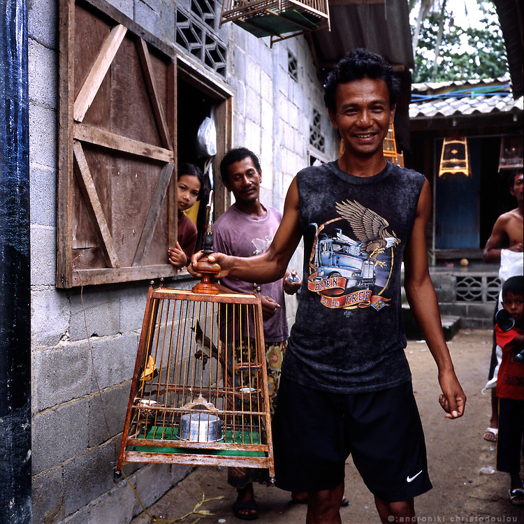 Man with birdcage in the fishermen's village that is attached to the city of Narathiwat, on the banks of Bang Nara river.