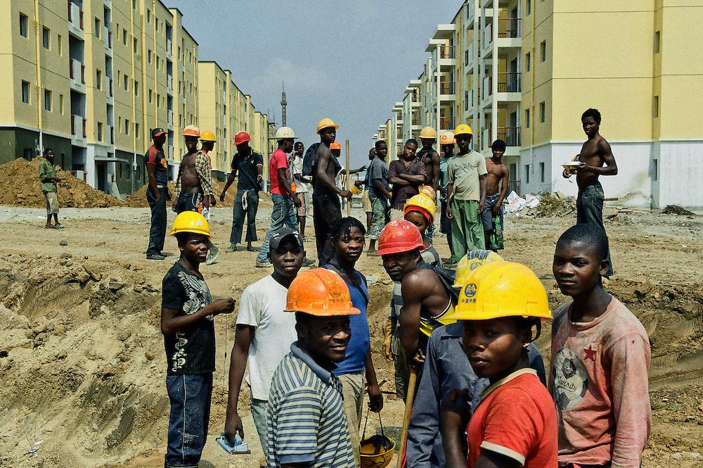 Trabalhadores serventes  angolanos que trabalham na construção da nova Centralidade de Cacuaco. A cidade está a ser construída por uma empresa chinesa chamada CTCE. Província de Luanda, Angola.