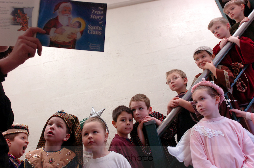 A teacher reads to students as they wait backstage before the St. Joseph School's Christmas pageant in Needham, MA.