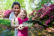 Allie Moyer catches a 5 pound largemouth bass on her very first cast into the pond; with her mother, Lisl at the Blitch family residence, Ahmeek, in Abita Springs, Louisiana
