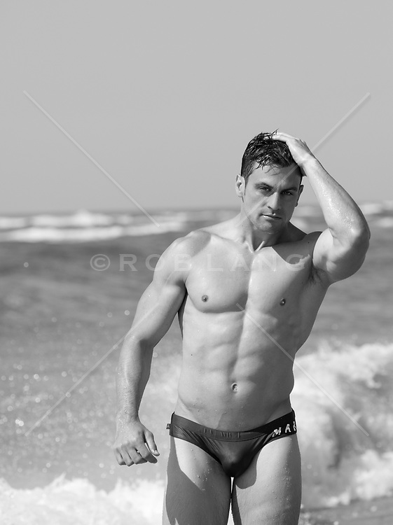 muscular man in a small bikini at the ocean