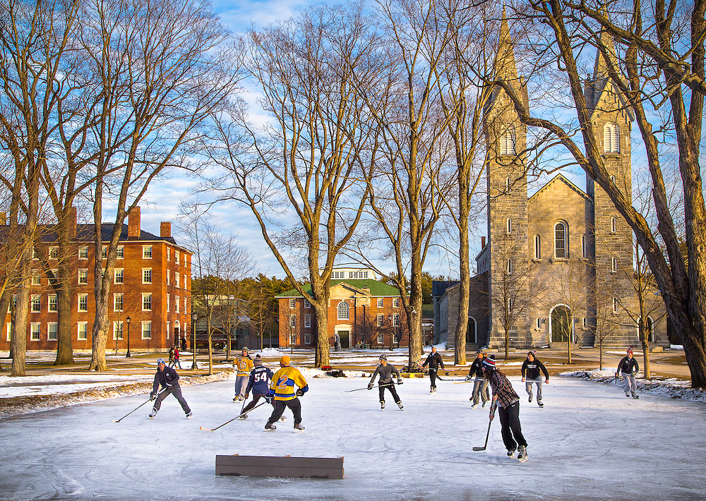 A group of students play a game of pick-up hockey on the skating rink on the Bowdoin College Quad.