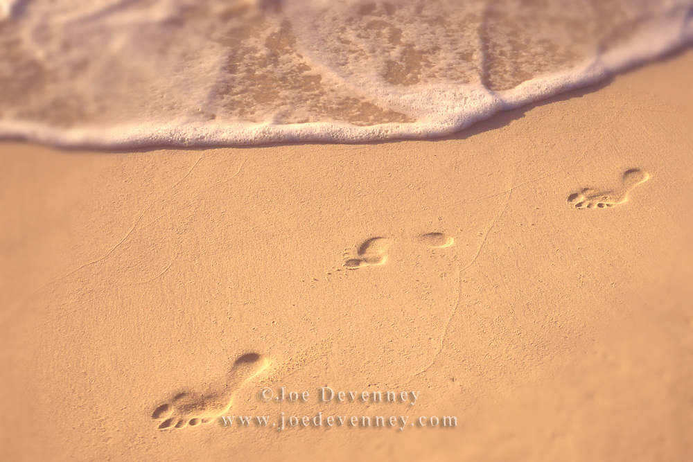 Footprints on a sandy beach with a wave washing the shore