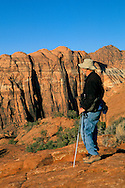 Hiker on slickrock above Snow Canyon, Snow Canyon State Park, Ivins, Utah's Dixie, near St. George, UTAH