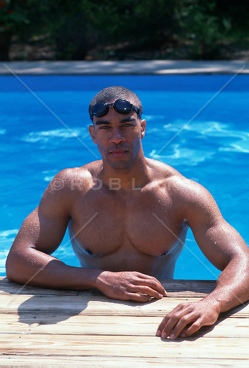 muscular African American man standing in the shallow end of a swimming pool