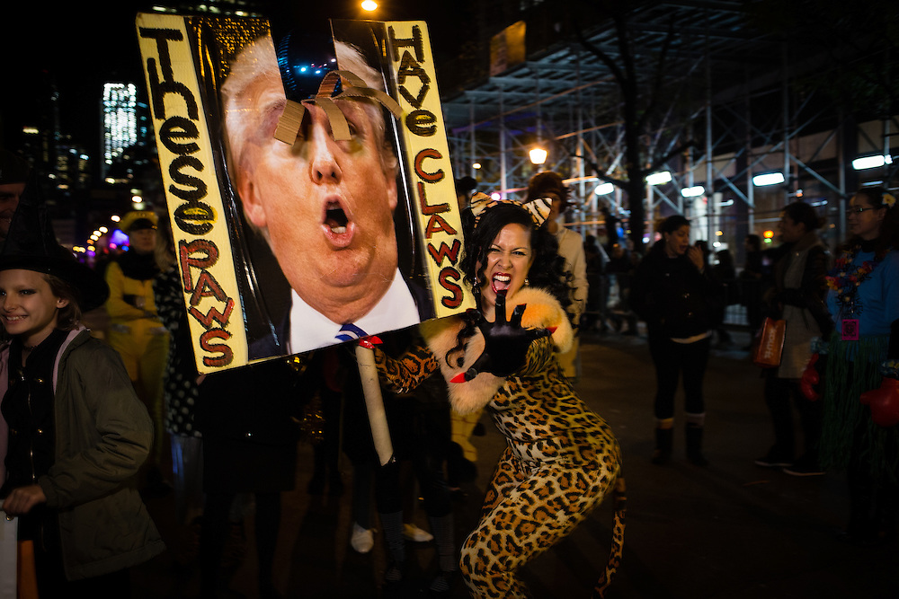 """New York, NY - 31 October 2016. Skater, performance artist and political activist Marni Halasa wears a cat suit and carries a sign with a mutilated photo of Donald Trump, the sign captioned """"These paws have claws."""""""