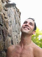 Mid adult man taking shower smiling outdoors