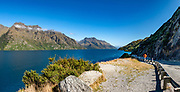 Driving along Lake Wakatipu towards Queenstown, Otago region, South Island of New Zealand. Queenstown Bay is on Lake Wakatipu, a long Z-shaped lake carved by glaciers. This image was stitched from multiple overlapping photos.