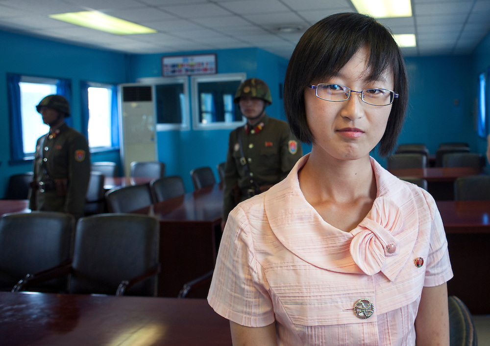 -(at the DMZ) A little smile Miss Kim!<br /> -i can't...<br /> -?<br /> -my heart is bleeding...<br /> <br /> North Korean woman visiting the Joint Security Area at Dmz, Panmunjom, North Korea.<br /> <br /> Miss Kim is 20. She lives in Pyongyang, North Korea's display window. She's studying English. First of her class, she was lucky enough to come with me during my 6th trip to North Korea as an assistant guide. She had never previously left Pyongyang. It was a unique opportunity for her to visit her own country and to get to meet and speak to a foreigner. She was shy at first, but became quite talkative as the days went on, and describe to me the everyday lives of young North Koreans. Without ever crossing over the Party line...<br /> <br /> Small chats between friends who will never meet again...<br /> <br /> Eric Lafforgue