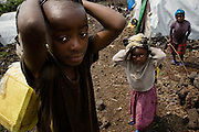 Children carry jericans of water on their backs in the Mugunga II IDP camp on the outskirts of Goma, Democratic Republic of Congo, on Wednesday December 17, 2008.