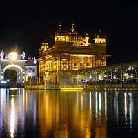 The sanctum of Sri Harmandir Sahib, covered in gold foil, and fully lit at night.