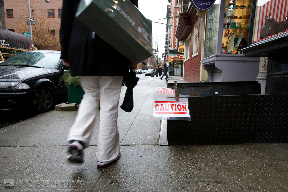 A shopper walks past a caution sign in the SoHo district of New York city