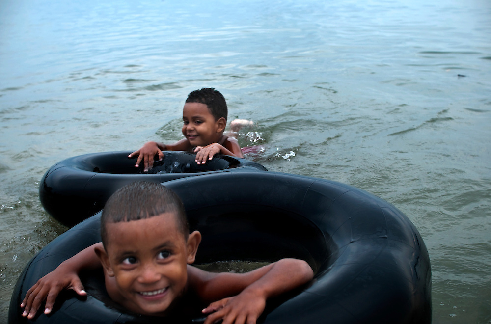 Local children swim near the recently refurbished boardwalk in Santa Marta, Colombia.