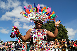 © Licensed to London News Pictures. 29/08/2016. Leeds, UK. A woman dressed in bright coloured feathers dances at the Leeds West Indian Carnival in Leeds, West Yorkshire. First run in the 1960's, the Leeds West Indian Carnival is Europe's longest running authentic Caribbean carnival parade. Photo credit : Ian Hinchliffe/LNP