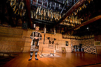 An Ainu man performs on a stage under a ceiling draped with dried fish.