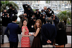 Moon Sori and Isabelle Huppert and Hong Sangsoo pose's for Photographers during the Photocall for the film In Another Country during 65th Annual Cannes Film Festival at Palais des Festivals, Cannes, France, Monday May 21, 2012. Photo by Andrew Parsons/i-Images