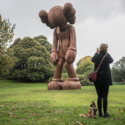 London, UK - 15 October 2014: a woman with a dog takes a picture at 'Small Lie' by New York-based artist KAWS during the first day of Frieze Art Fair and Frieze Masters in Regent's Park.